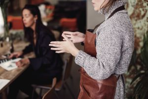 florentine leather: female owner gesturing while standing at workshop